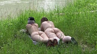Voyeur outdoors peeps at two naked lesbians. Nudists with big asses sunbathe and enjoy nature and masturbation.